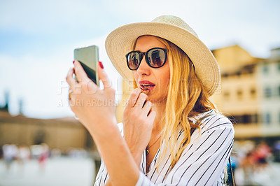 Buy stock photo Shot of a woman applying lipstick using her cellphone as a mirror