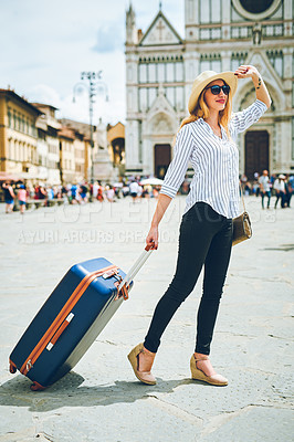 Buy stock photo Shot of a woman walking around in a foreign city with her suitcase