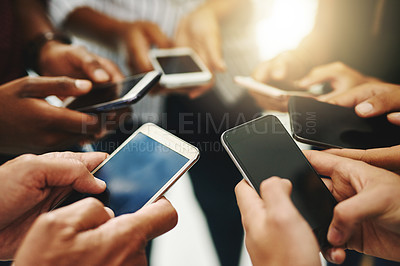Buy stock photo Closeup shot of a group of unrecognizable businesspeople using their cellphones in synchronicity