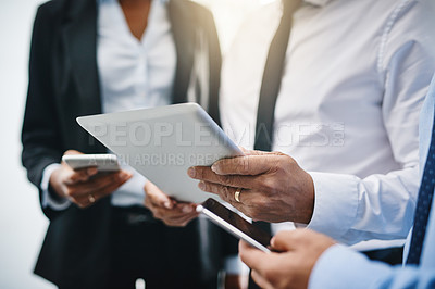 Buy stock photo Cropped shot of an unrecognizable group of businesspeople standing together and using technology in the office