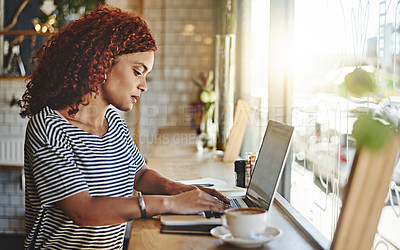 Buy stock photo Cropped shot of an attractive young businesswoman sitting alone and blogging from her laptop while inside a cafe