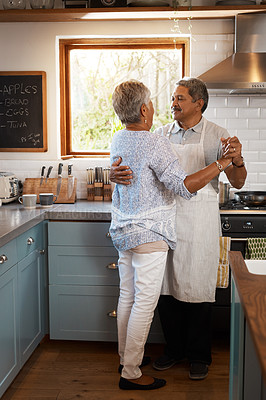 Buy stock photo Shot of a happy mature couple dancing together while cooking in the kitchen at home
