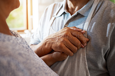 Buy stock photo Cropped shot of a mature man holding his wife's hand close to his heart in the kitchen at home