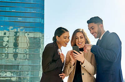 Buy stock photo Shot of three young businesspeople standing and  using a cellphone together in the city