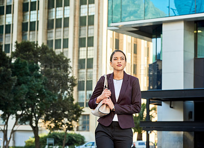 Buy stock photo Shot of an attractive and confident young businesswoman walking in the city during the day