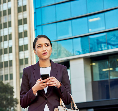 Buy stock photo Shot of an attractive young businesswoman using a cellphone while walking through the city