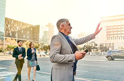 Buy stock photo Shot of a mature businessman gesturing for a cab in the city