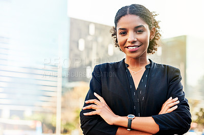 Buy stock photo Portrait of an attractive young businesswoman posing with her arms folded in the city