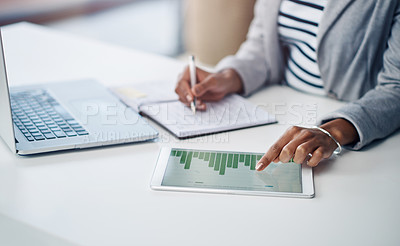 Buy stock photo Shot of an unrecognizable businesswoman using a digital tablet with graphs on it in a modern office