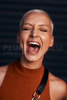 Buy stock photo Cropped shot of an attractive young woman screaming while standing against a dark background