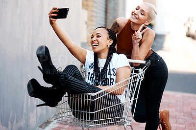 Buy stock photo Cropped shot of two cheerful young girlfriends taking a selfie while playing around with a shopping cart outdoors