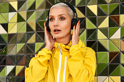 Buy stock photo Cropped shot of an attractive young woman standing against a tiled wall and listening to music through headphones