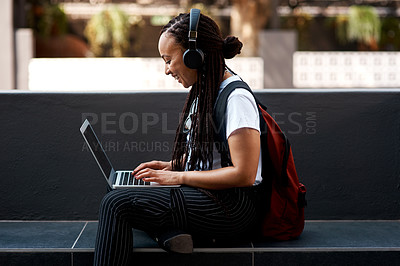 Buy stock photo Shot of an attractive young woman listening to music and using her laptop while relaxing outdoors