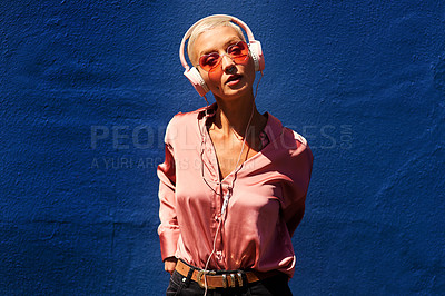 Buy stock photo Cropped portrait of an attractive young woman standing against a blue wall and listening to music through headphones