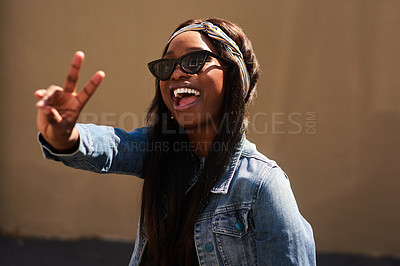 Buy stock photo Cropped portrait of an attractive young woman wearing sunglasses and making a peace sign while standing against a wall alone