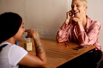 Buy stock photo Shot of two attractive young women catching up and relaxing together inside a cafe