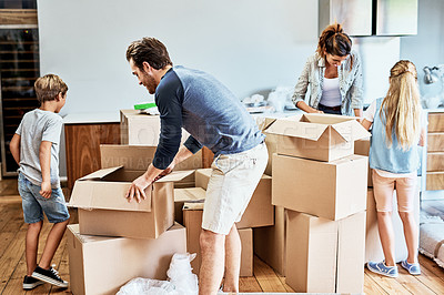 Buy stock photo Cropped shot of a focused young family of four working together to unpack boxes in their new home on moving day