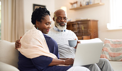 Buy stock photo Shot of a mature couple using a laptop together on the sofa at home