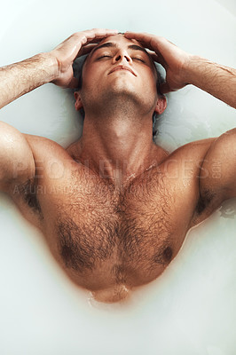 Buy stock photo High angle shot of a handsome young man lying in a bathtub full of milky water at home