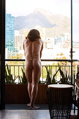 Buy stock photo Rearview shot of an unrecognizable muscular man standing at the balcony of a guest house during the day