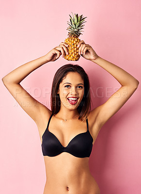 Buy stock photo Studio shot of a beautiful young woman balancing a pineapple on her head against a pink background
