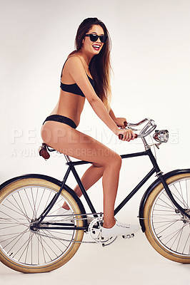 Buy stock photo Studio shot of a beautiful young woman riding a bicycle in her underwear