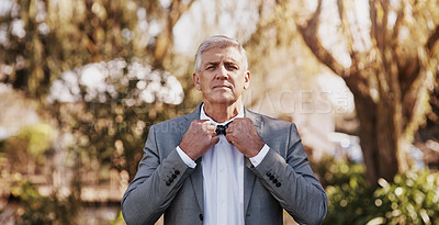 Buy stock photo Cropped portrait of a handsome mature bridegroom adjusting his necktie while preparing for his wedding outdoors