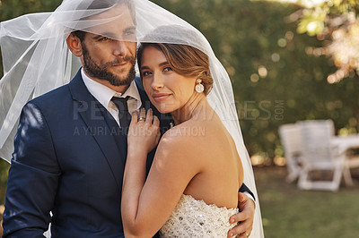 Buy stock photo Cropped shot of an affectionate young newlywed couple embracing each other while covering themselves with a veil on their wedding day