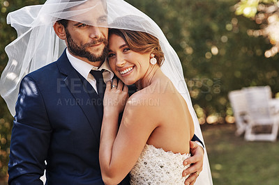 Buy stock photo Cropped shot of an affectionate young bride smiling embracing her groom under a veil on their wedding day