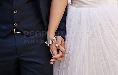 Buy stock photo Cropped shot of an unrecognizable newlywed couple holding hands while standing outdoors on their wedding day