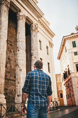 Buy stock photo Cropped shot of an unrecognizable man standing alone and looking at an ancient building during a day out in Rome