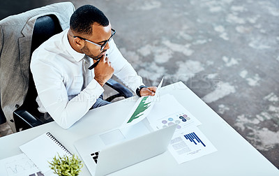Buy stock photo Cropped shot of a handsome young businessman sitting in his office and looking contemplative while reading paperwork
