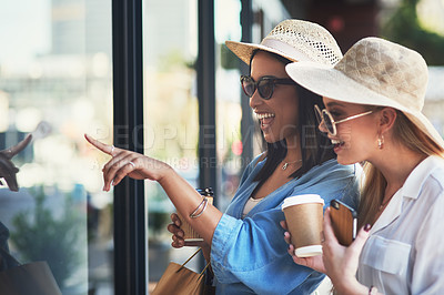 Buy stock photo Cropped shot of two attractive young girlfriends window shopping together in the city during the day