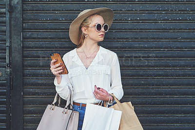 Buy stock photo Cropped shot of an attractive young woman looking away thoughtfully while holding a smartphone and shopping bags against an urban background