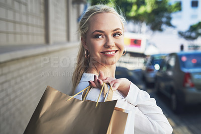 Buy stock photo Cropped shot of an attractive young woman looking away thoughtfully while holding shopping bags in the city during the day