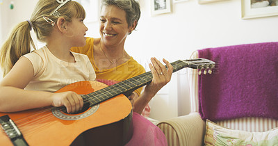 Buy stock photo Shot of a senior woman playing the guitar with her granddaughter