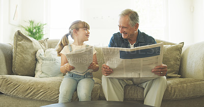 Buy stock photo Shot of a young girl and her grandfather reading the newspaper while sitting in the living room