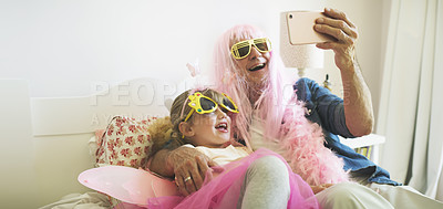 Buy stock photo Shot of a senior man taking selfies with his granddaughter while playing dress up at home