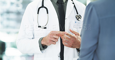 Buy stock photo Cropped shot of an unrecognizable male doctor consulting a female patient while standing in a hospital