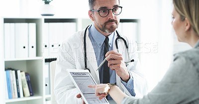 Buy stock photo Cropped shot of a handsome middle aged male doctor going through a nutritional facts table on a digital tablet with a female patient in his office