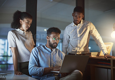 Buy stock photo Cropped shot of a group of young businesspeople using a laptop together while working late in a modern office