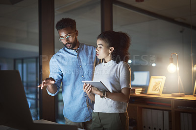 Buy stock photo Cropped shot of two young businesspeople having a discussion while using a computer and a digital tablet in an office at night