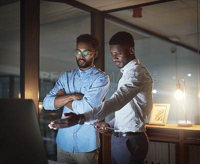 Buy stock photo Cropped shot of two handsome young businessmen having a discussion while using a computer and a digital tablet in an office at night