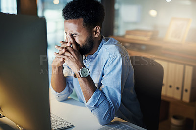 Buy stock photo Shot of a young businessman rubbing his eyes while working on a computer in an office at night