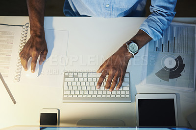 Buy stock photo High angle shot of an unrecognisable businessman working on a computer in an office at night