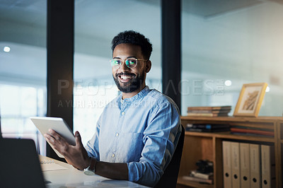 Buy stock photo Portrait of a young businessman using a digital tablet in an office at night