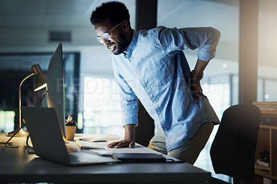 Buy stock photo Shot of a young businessman experiencing back pain while working in an office at night