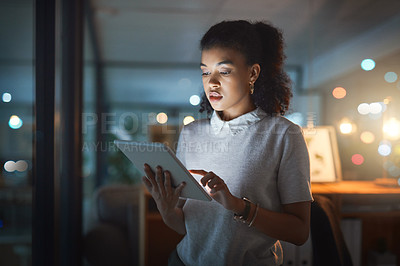 Buy stock photo Shot of a young businesswoman using a digital tablet while working late in her office