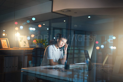 Buy stock photo Shot of a businesswoman using a computer while working late in her office