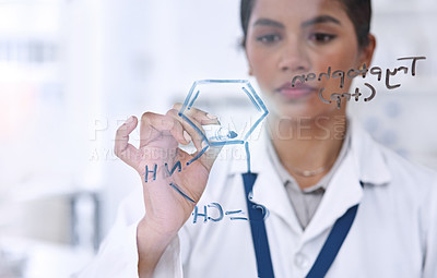 Buy stock photo Cropped shot of an attractive young female scientist working on formulas in her laboratory